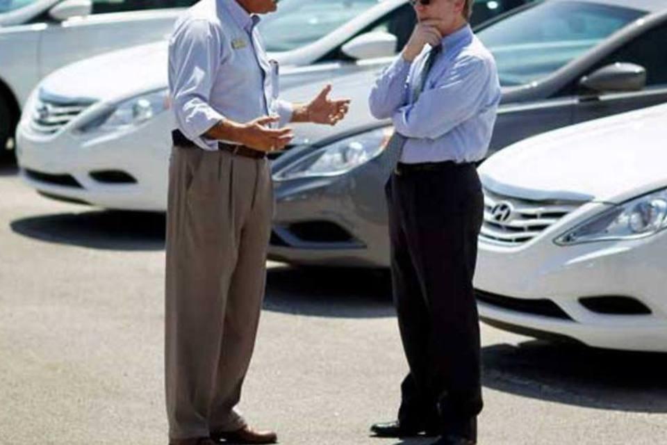Homens conversando em um pátio com carros