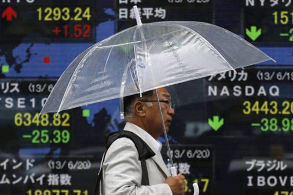 Homem segurando um guarda-chuva passa por um quadro eletrônico mostrando as cotações do índice Nikkei e de outras bolsas do mundo, em Tóquio no Japão