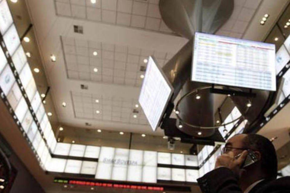 Homem conversa ao celular e observa tela eletrônica na bolsa de valores BM&FBovespa, em São Paulo