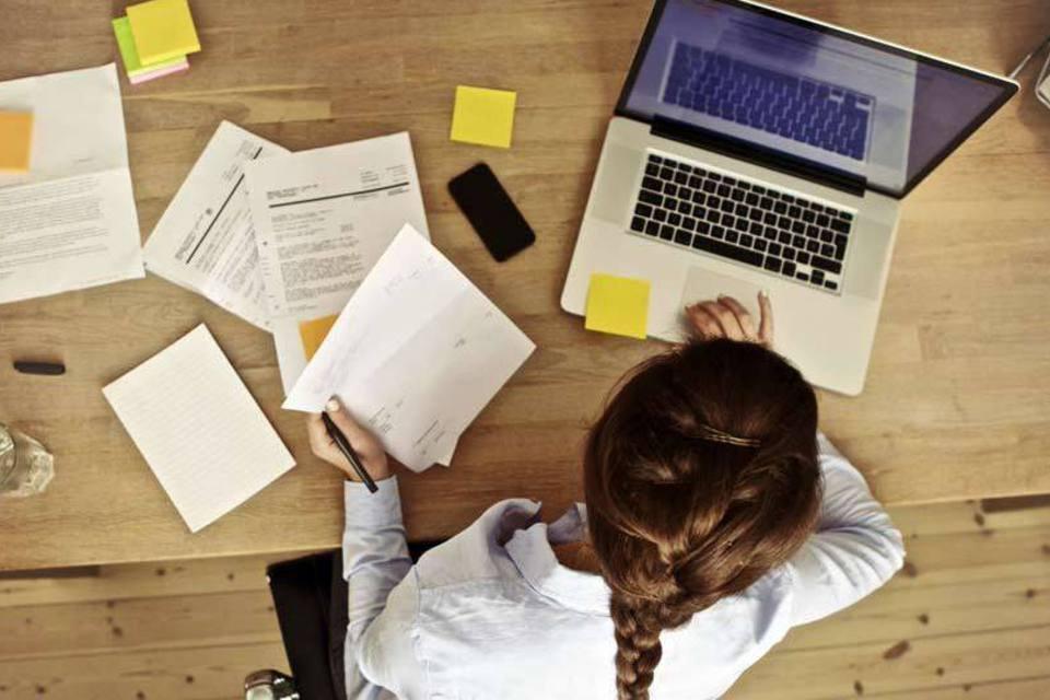 Mulher trabalha em computador, com papéis ao lado