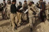 Forças de segurança carregam o corpo de um homem que morreu após um ataque em uma base aérea na cidade de Quetta, no Paquistão