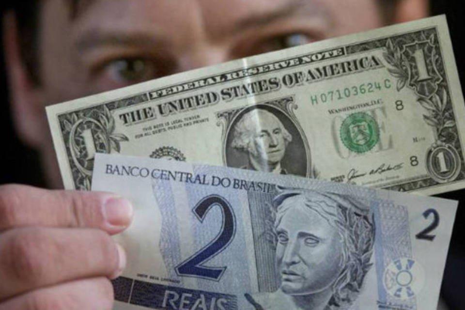 Câmbio: homem segura notas de dólar e real