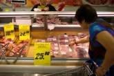 Consumidora escolhendo carne em um supermercado em Hong Kong, na China