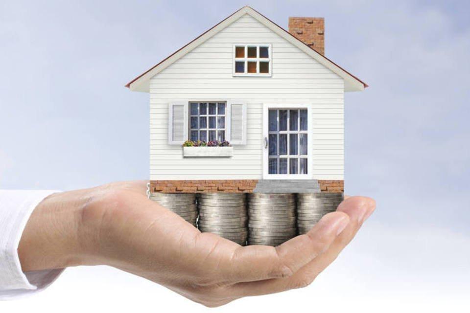 Homem segura moedas e casa em miniatura