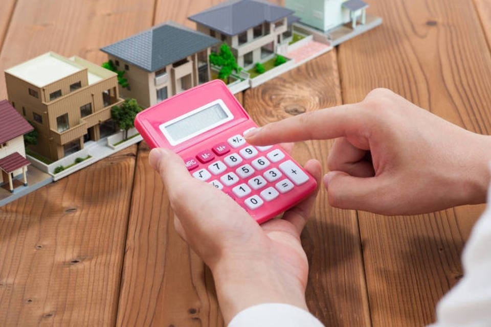 Casas e calculadora representando custos do financiamento de imóveis
