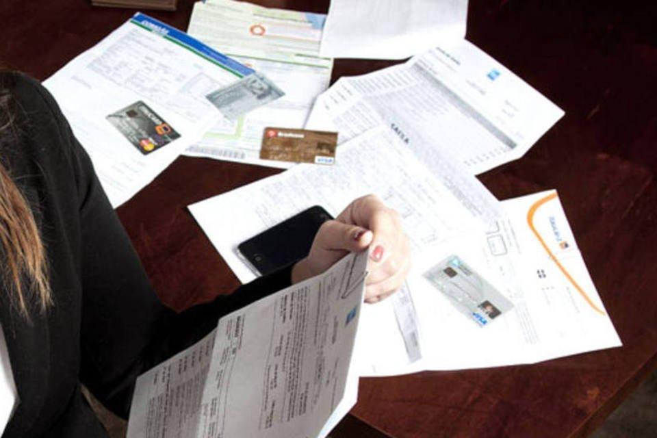 Mulher olha documentos e contas