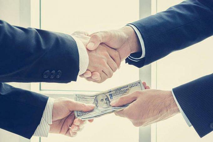 Homem paga nota de dólar a outra e dá aperto de mão (acordo monetário)