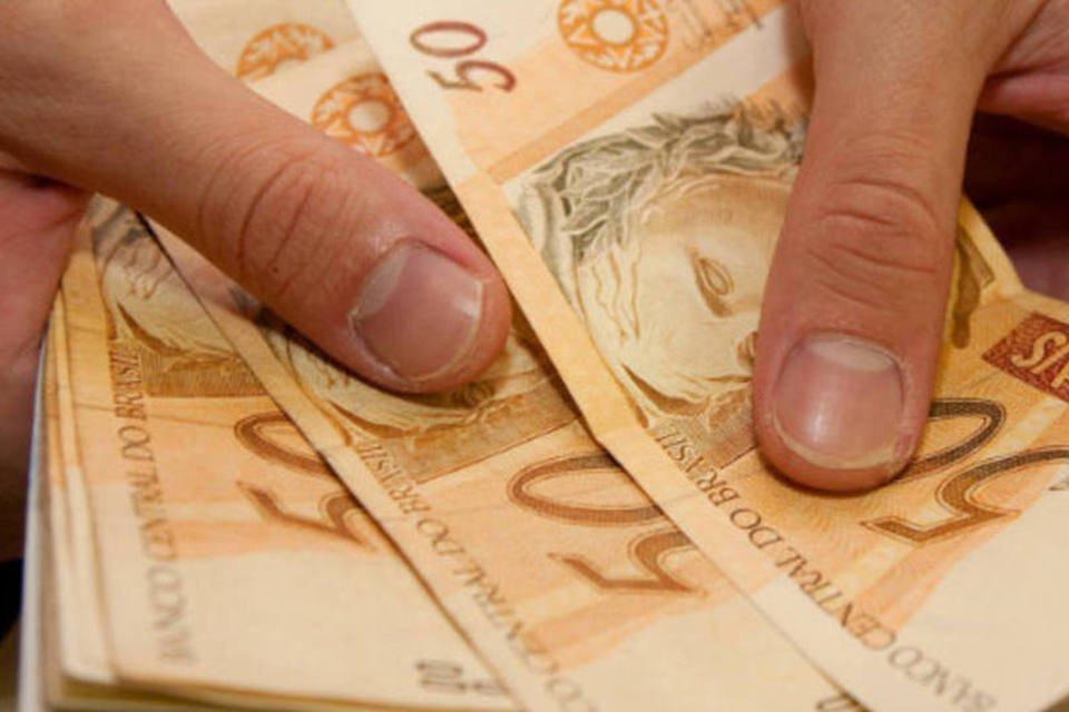 Pessoa conta notas de cinquenta reais - dinheiro