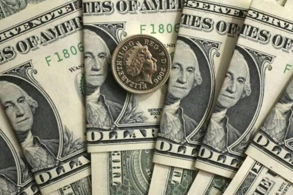Dólares em notas embaixo de uma moeda de libra
