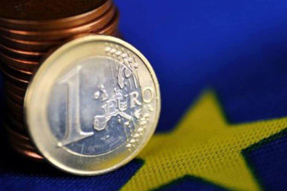 Moedas de euro sobre bandeira da União Europeia