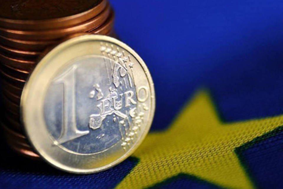Moedas de euro sobre a bandeira da União Europeia