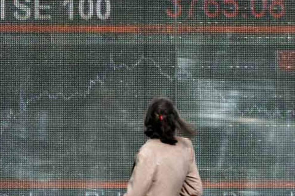 Mulher olha painel com movimento do índice FTSE 100, da bolsa de Londres, em outubro de 2008