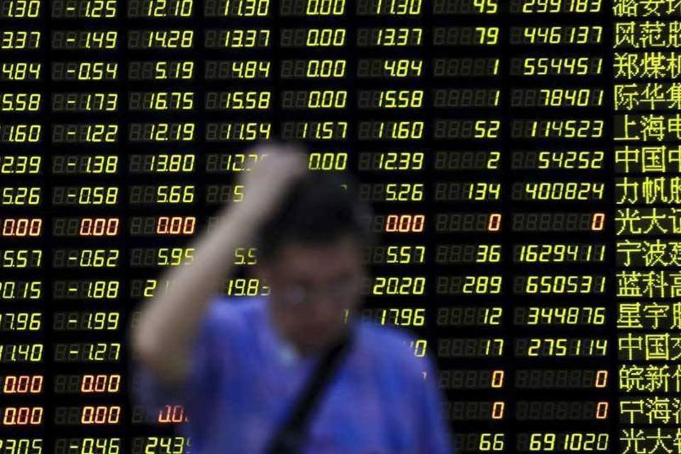 Investidor em Xangai, na China, em frente a painel que mostra recuo da bolsa
