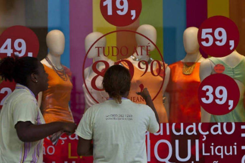 Comércio: consumidoras olham vitrine de loja de roupas em promoção