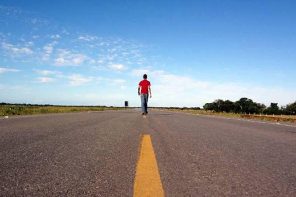 Homem caminha em estrada