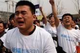 Parentes das vítimas do voo MH370 choram durante protesto em frente à embaixada da Malásia em Pequim
