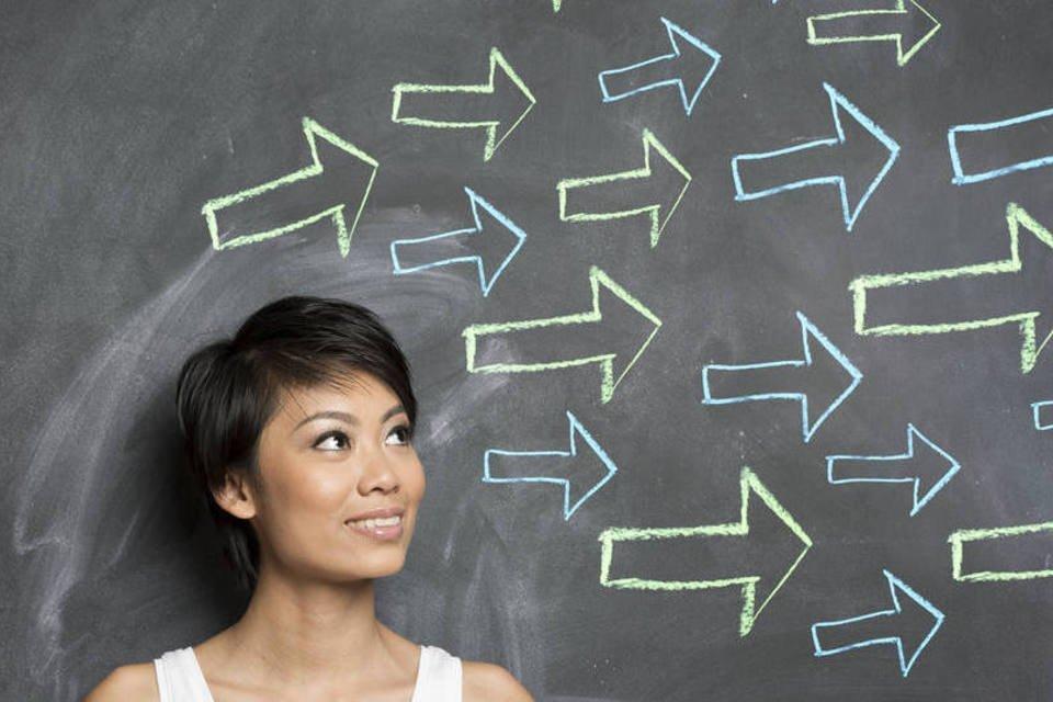 Mulher em frente a quadro negro com flechas desenhadas, indicando alternativas