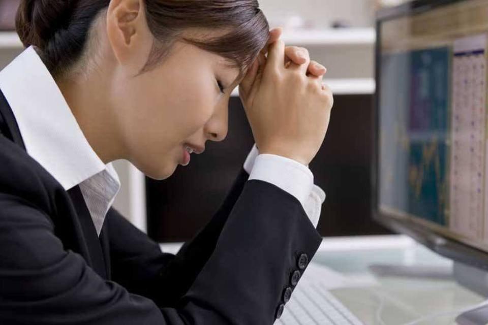 Empreendedora olha planilhas e gráficos em tela de computador com preocupação