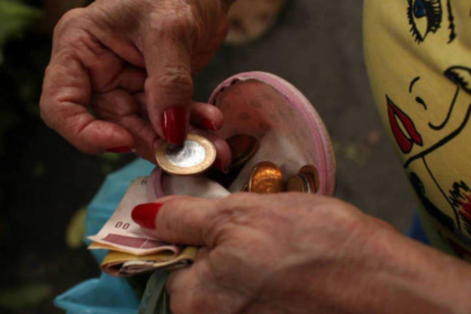 Comércio: mulher conta dinheiro de Real na carteira