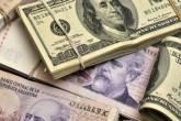 Notas de 100 pesos argentinos com notas de 100 dólares em um foto arranjada em Buenos Aires, Argentina