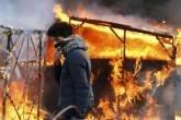 Refugiado em frente a abrigos incendiados em protesto, em Calais, França, dia 29/02/2016