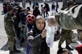 Refugiada recebe porção de comida e água no campo de refugiados na Grécia, dia 25/02/2016