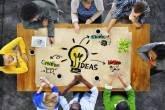 Grupo (equipe) trabalhando em ideias (startup) ao redor de mesa