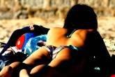 Moça toma Sol de costas na praia