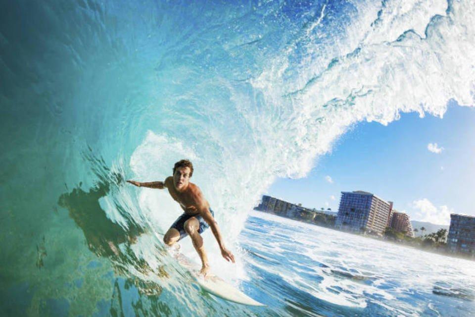 Homem surfando em onda na praia