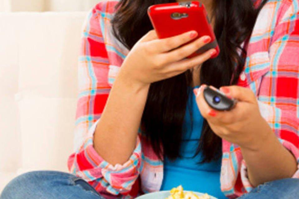 Pessoa usa controle remoto e celular ao mesmo tempo