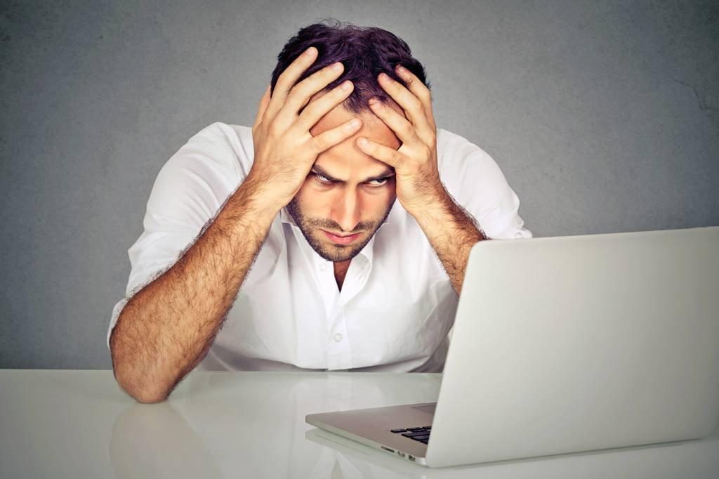 Homem estressado em frente a um notebook