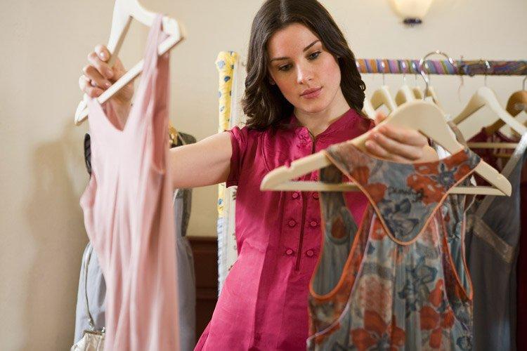 Mulher se decide entre duas peças de roupa em loja