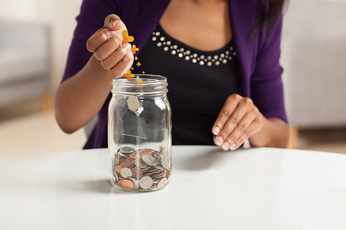 Mulher guarda dinheiro em pote com símbolos do Inmais