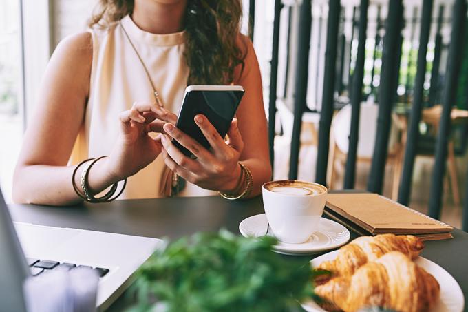Mulher usando smartphone sentada em uma mesa com um notebook, um café e pães