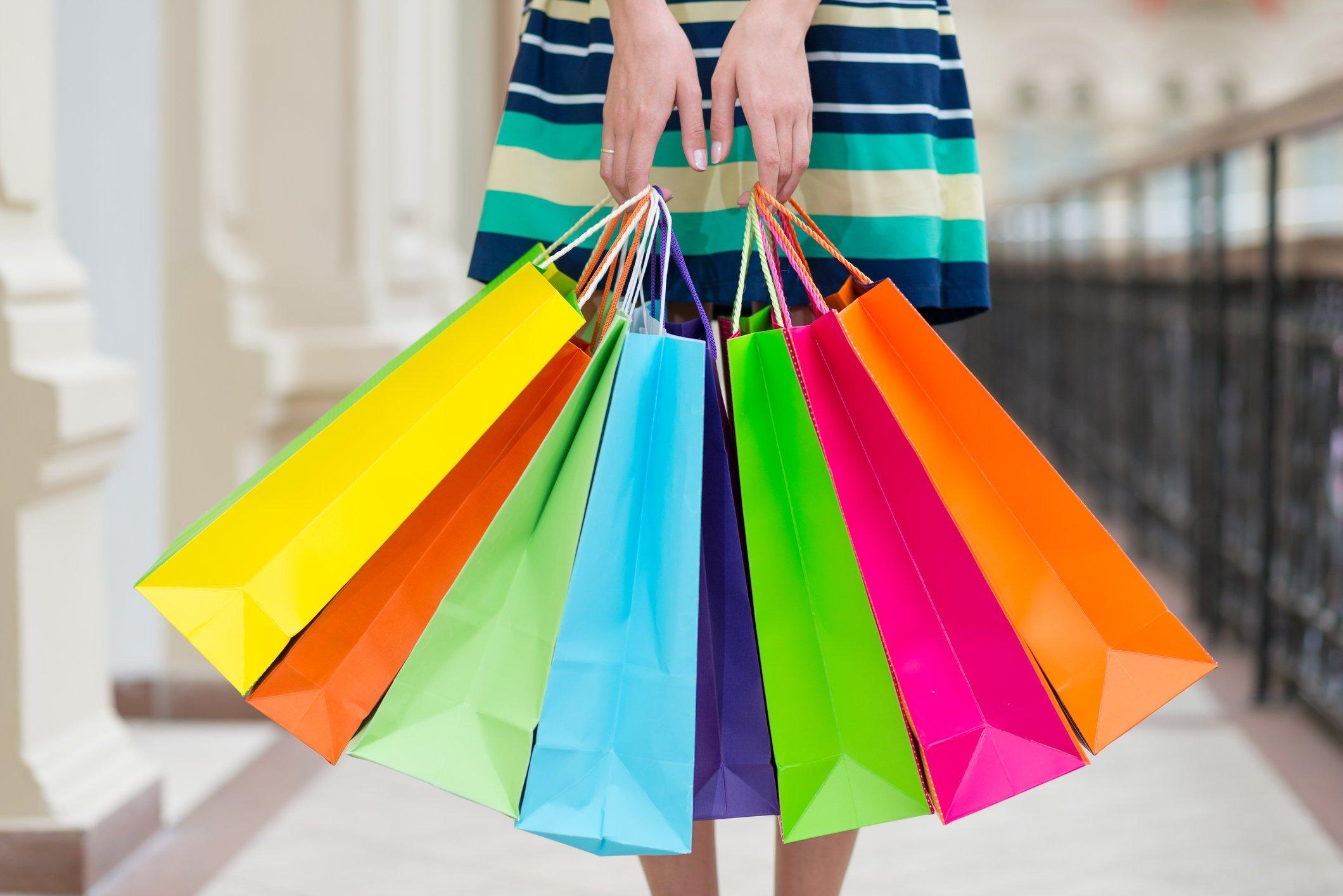Mulher segura sacolas na liquidação
