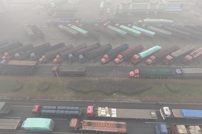 Caminhões são vistos encalhados perto de uma estrada durante um dia poluído em Shijiazhuang, província de Hebei, na China em 20 de dezembro de 2016.
