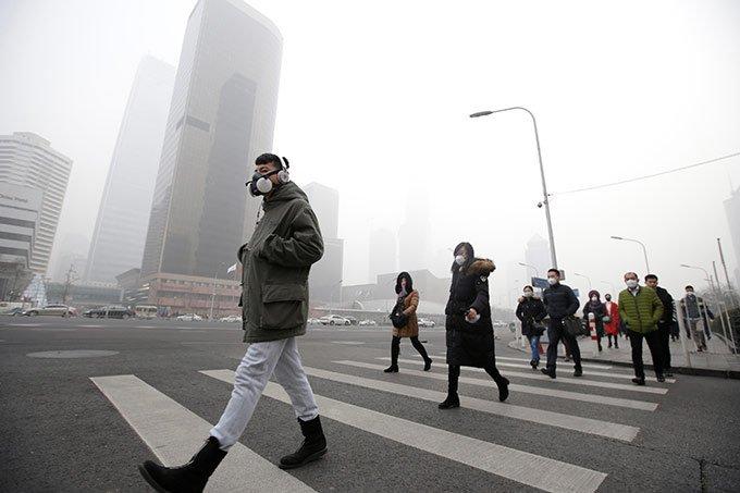 Pessoas usam máscaras de proteção contra poluição pesada em Pequim, China, em 21 de dezembro de 2016.