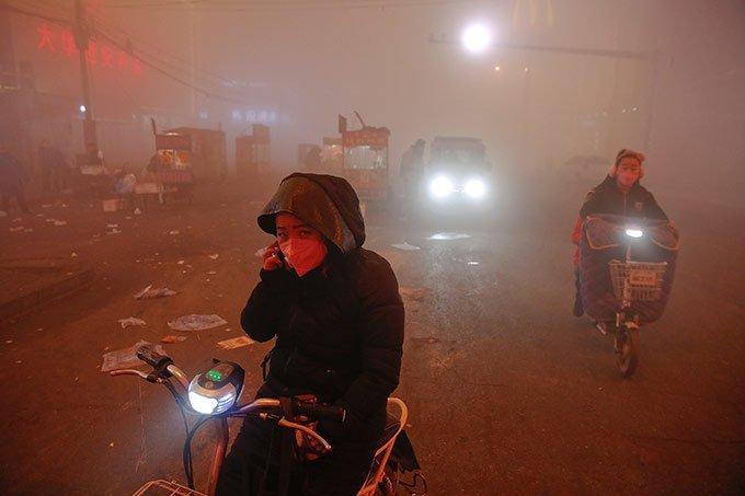 Em Shengfang, província de Hebei, na China, pessoas enfrentam poluição intensa em um dia extremamente poluído com alerta vermelho.