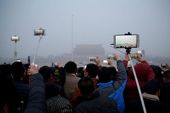 Pessoas gravam cerimônia de hasteamento de bandeira durante a poluição atmosférica na Praça Tiananmen depois que um alerta vermelho foi emitido para a poluição do ar em Pequim, China, 20 de dezembro de 2016.
