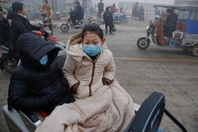Pessoas usam máscaras de proteção contra poluição pesada na província de Hebei, China, em 20 de dezembro de 2016.