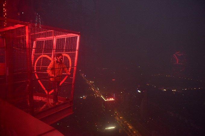 Um homem observa a cidade poluida do alto de uma torre da tevê em Chengdu, província de Sichuan, dezembro 20, 2016.