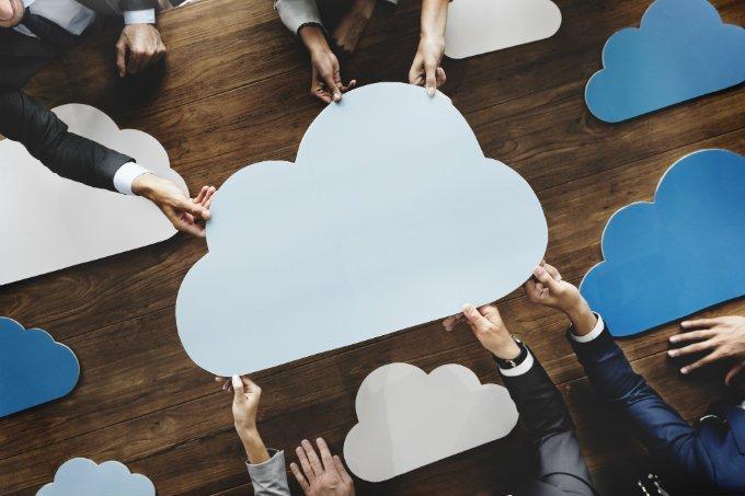 Mãos seguram nuvens de papel (computação em nuvem)