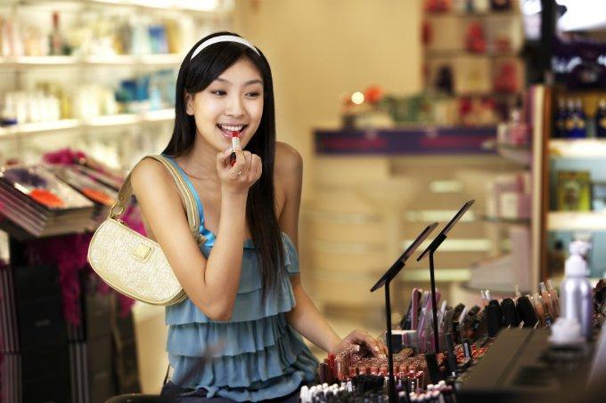 Mulher prova batom em loja de cosméticos (beleza, maquiagem)