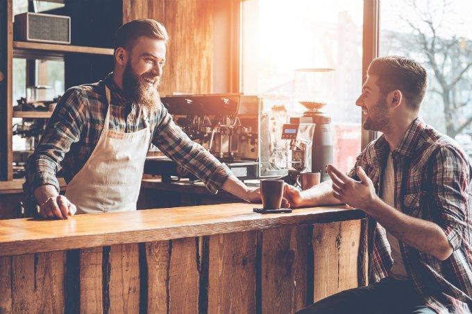 Empreendedor conversa com cliente em balcão de cafeteria