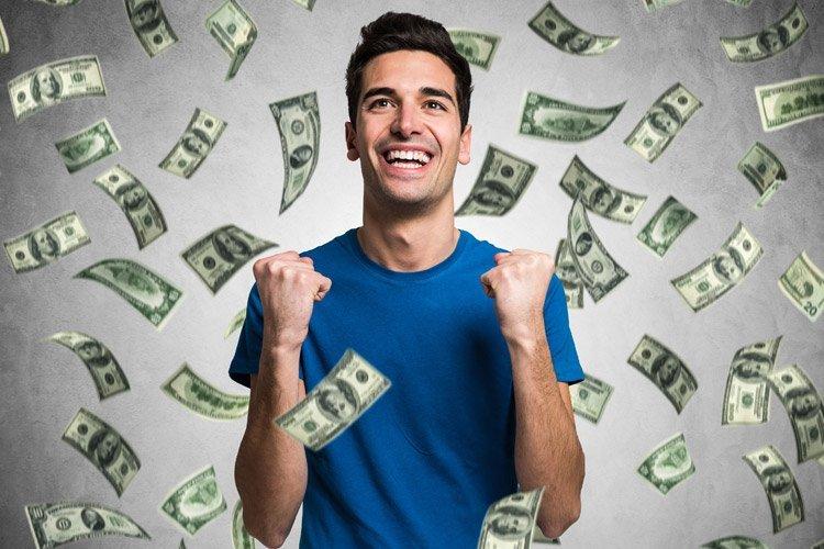 Homem feliz rodeado por notas de dinheiro