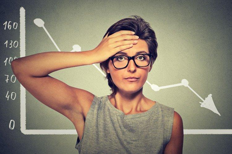 Gráfico em queda e pessoa/executiva/empreendedora preocupada: prejuízo, falência, queda