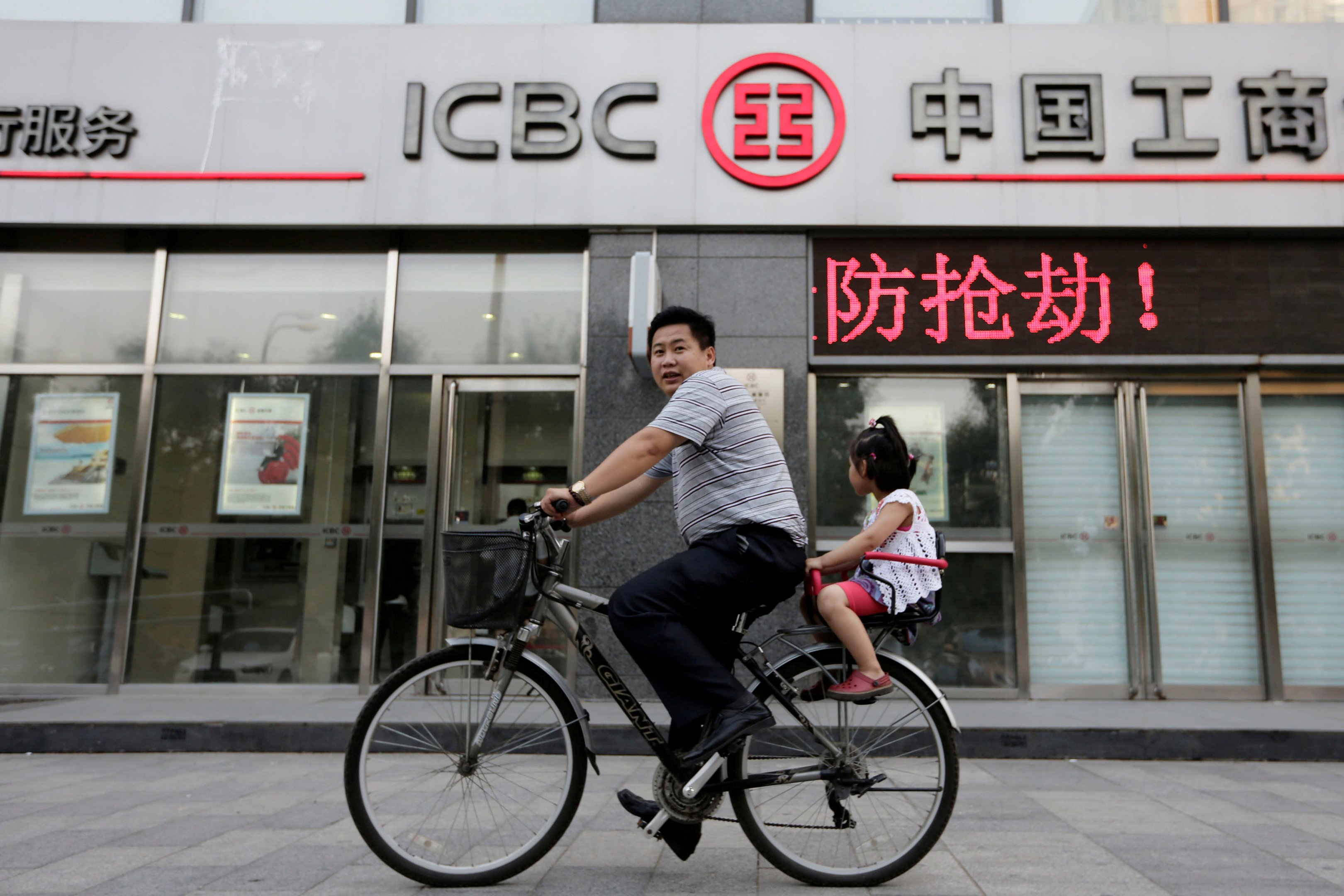 Homem e filha andam de bicicleta na frente de uma agência do banco ICBC, em Pequim, dia 26/06/2013