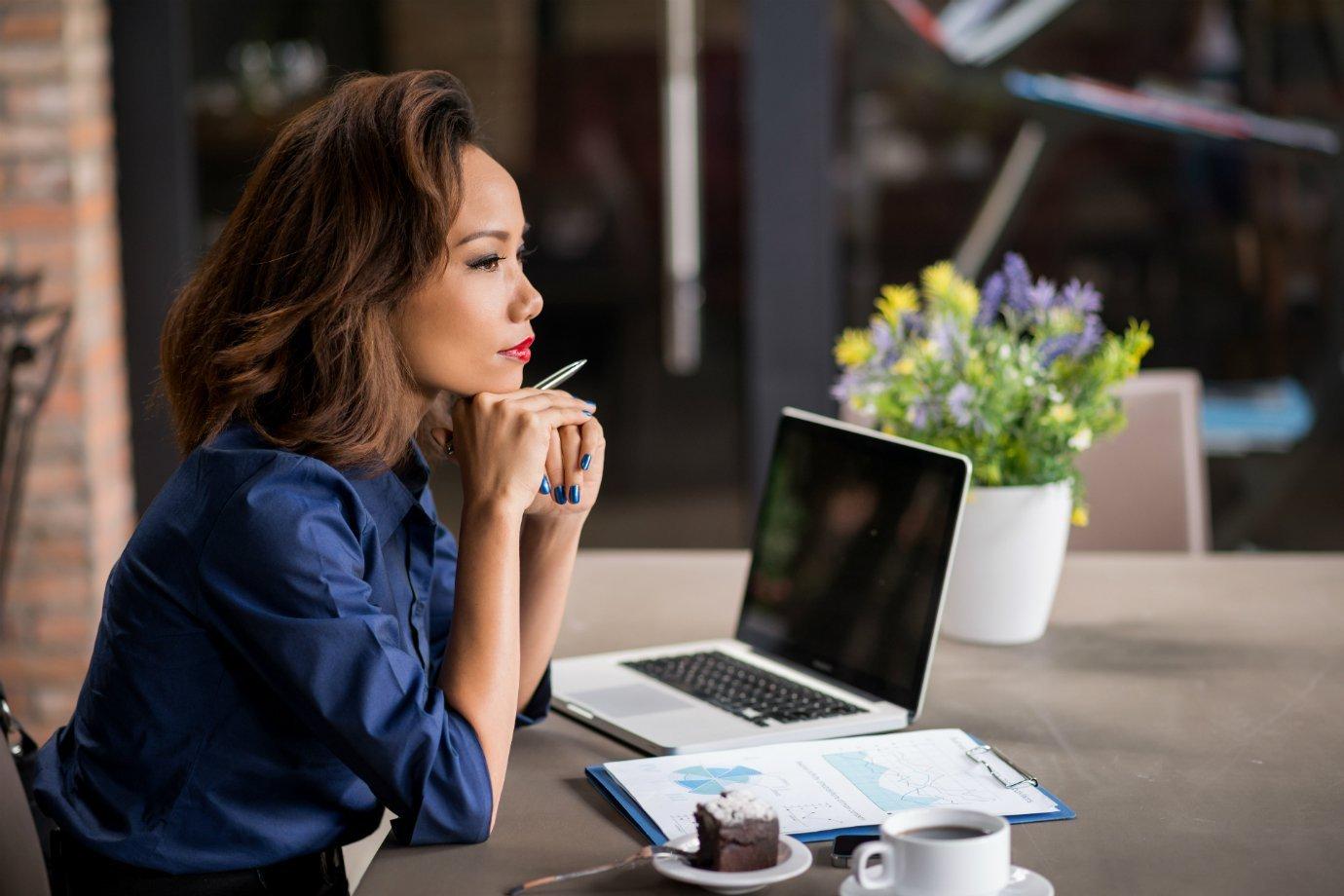 Mulher usa computador, pensando