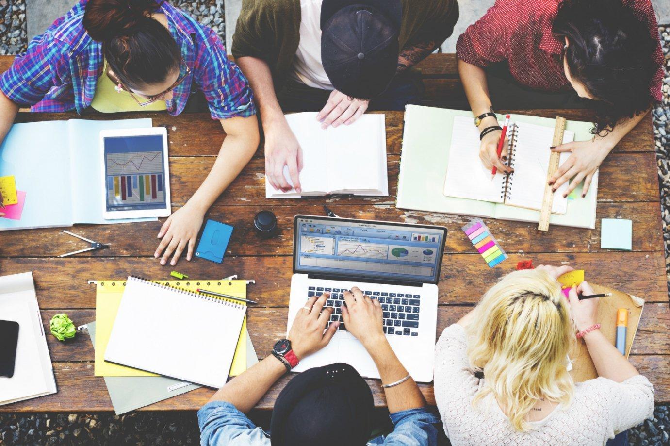 Empreendedores usam computadores, cadernos e post-its em mesa de trabalho: planejamento, reunião, startups