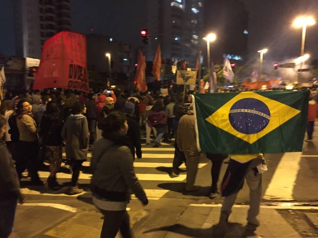 Manifestante segura bandeira do Brasil em protesto contra reformas em 28/04